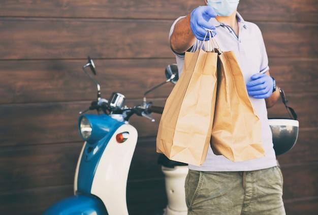 Il ragazzo delle consegne consegna il cibo al cliente con il suo ciclomotore
