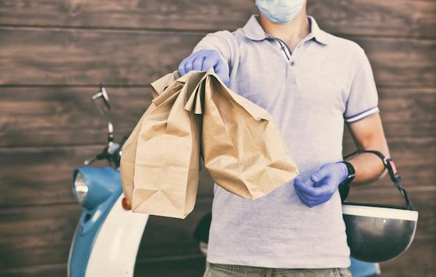 Il ragazzo delle consegne consegna cibo al cliente con un motorino