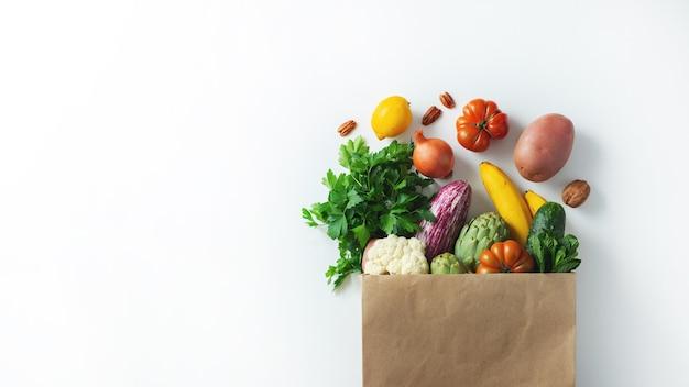 Consegna cibo vegetariano vegano sano in sacchetto di carta frutta e verdura su bianco. shopping supermercato alimentare e concetto di cibo vegano pulito.