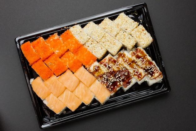 Consegna di cibo giapponese a casa. set di involtini con anguilla, salmone, formaggio, caviale di pesce volante, sesamo