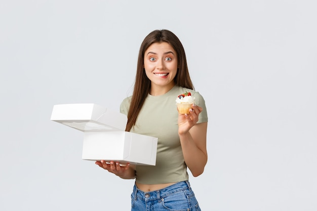 Consegna, stile di vita e concetto di cibo. donna carina allegra scatola aperta ordine dalla pasticceria e provando dolce delizioso cupcake, sorridendo e mordendosi il labbro dalla tentazione, in piedi sfondo bianco