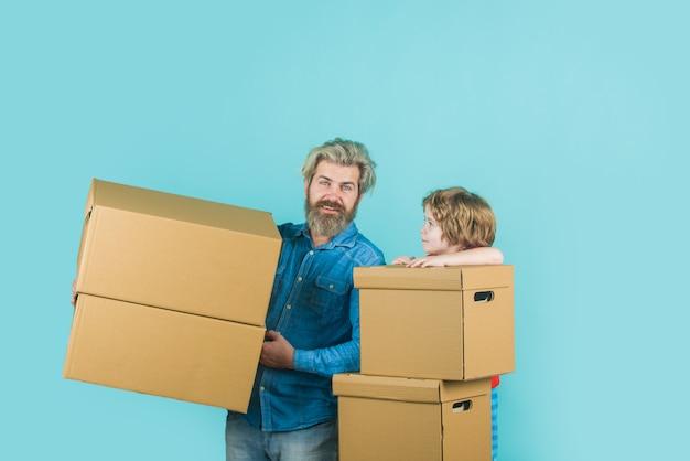 Posta di consegna uomo e ragazzo barbuti portano scatole figlio e padre felici con scatola di cartone internet
