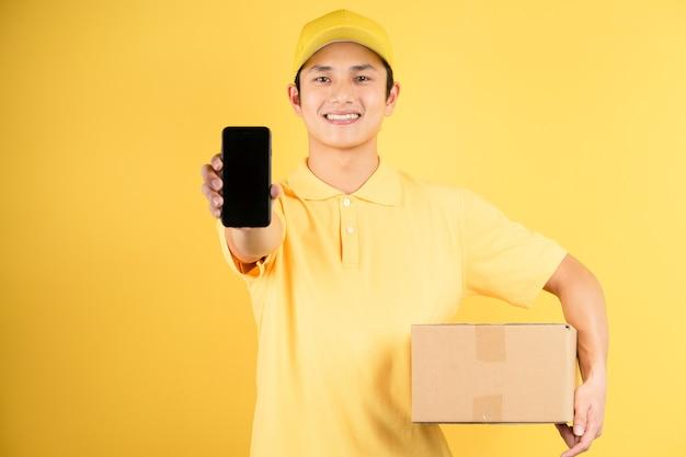 Ritratto maschio di consegna che tiene il contenitore di carico e che tiene il telefono in avanti sulla parete gialla