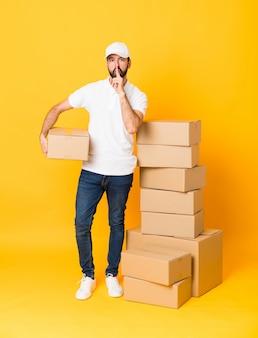 Uomo di consegna tra scatole che mostrano un segno di silenzio gesto mettendo il dito in bocca