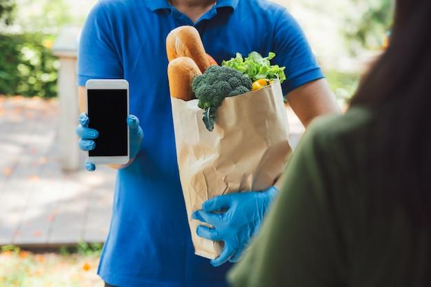 Il fattorino in camicia blu consegna il telefono al cliente confermare la ricezione del prodotto
