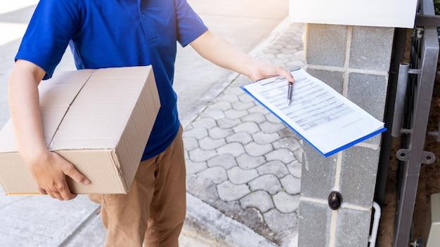 Uomo di consegna in uniforme blu che passa la cassetta dei pacchi per la lista di controllo di firma del cliente