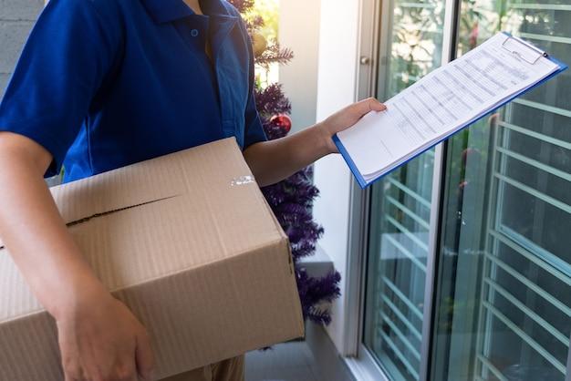 Uomo di consegna in uniforme blu che passa la cassetta dei pacchi per il cliente