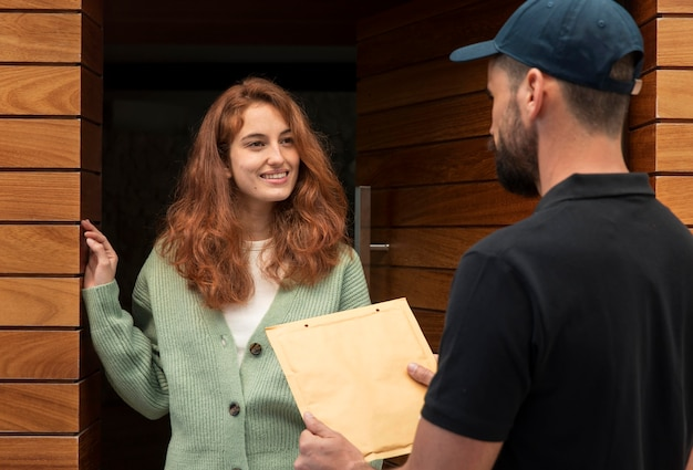 Uomo di consegna che consegna un pacchetto per una donna