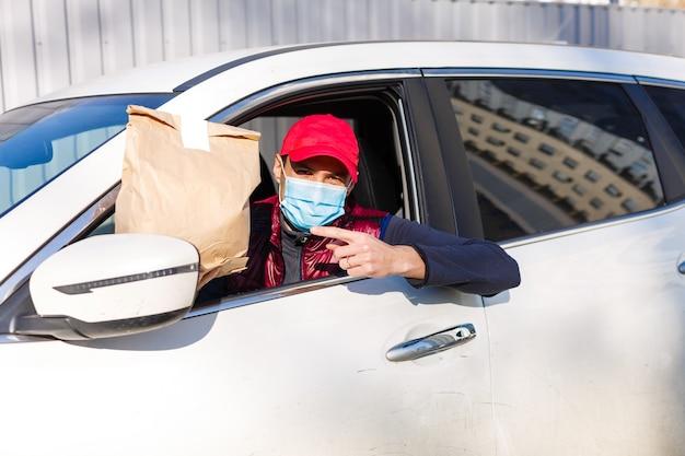 Il fattorino consegna gli ordini in auto. servizio di consegna in quarantena, focolaio di malattia, condizioni di pandemia di coronavirus covid-19.