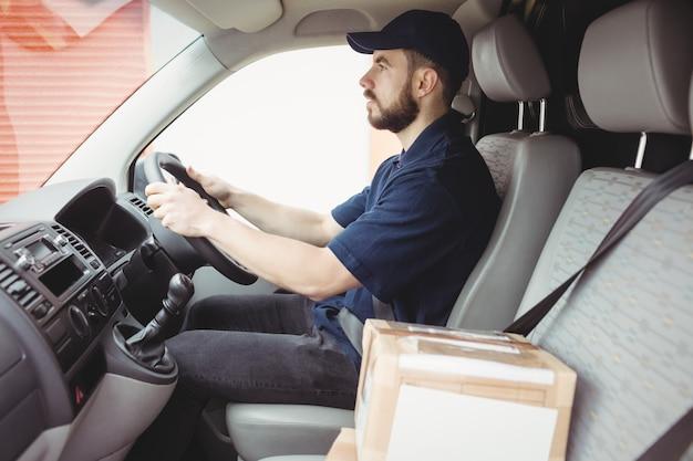 Uomo di consegna alla guida del suo furgone con un pacchetto sul sedile anteriore