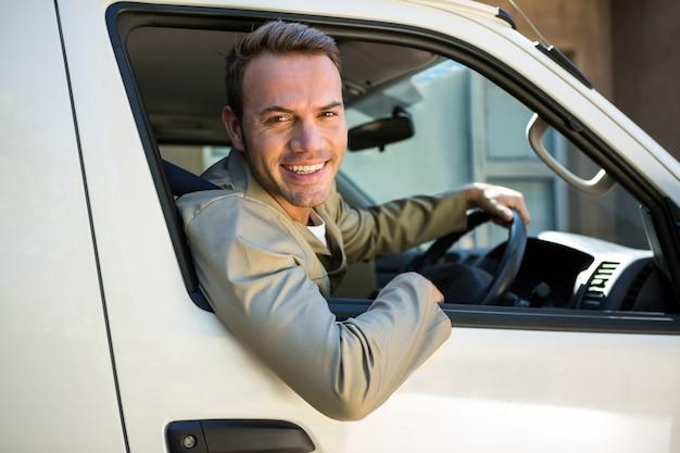 Uomo di consegna guida nel suo furgone