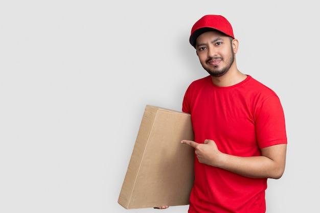 Dipendente dell'uomo di consegna in uniforme del dito della maglietta in bianco del cappuccio rosso tenere la scatola di cartone vuota isolata su fondo bianco