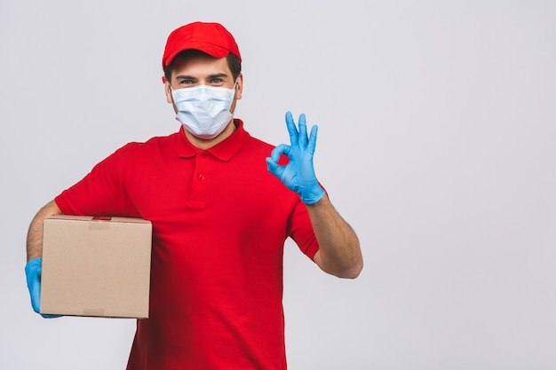 L'impiegato del fattorino in guanti della maschera di protezione dell'uniforme della maglietta dello spazio in bianco dello spiritello malevolo tiene la scatola di cartone vuota isolata sulla parete bianca. servizio quarantena pandemia coronavirus virus 2019-ncov concept.