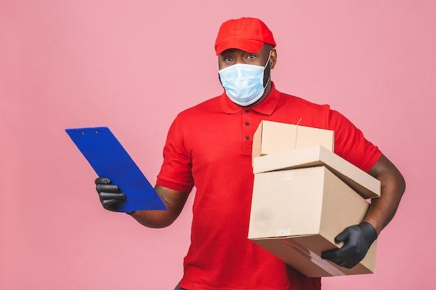 L'impiegato del fattorino in guanti della maschera di protezione dell'uniforme della maglietta in bianco del cappuccio rosso tiene la scatola di cartone vuota