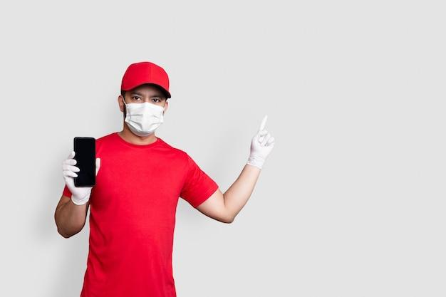 Dipendente del fattorino in maschera facciale uniforme della maglietta in bianco del cappuccio rosso in attesa dell'applicazione del telefono mobile nera isolata su fondo bianco