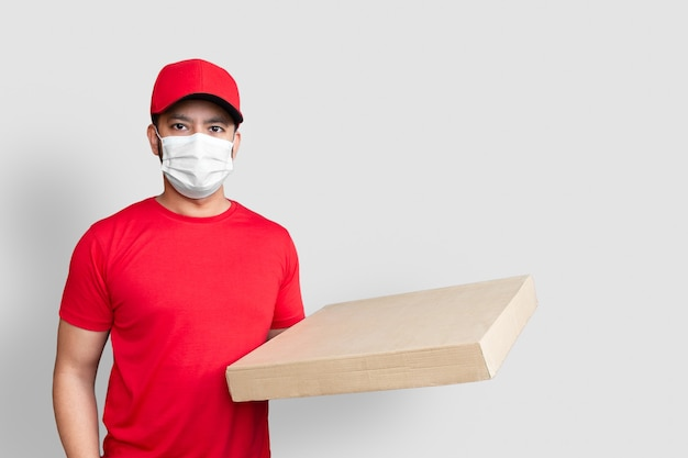 Dipendente dell'uomo di consegna nella maschera facciale uniforme della maglietta in bianco del cappuccio rosso tiene la scatola di cartone vuota isolata su fondo bianco