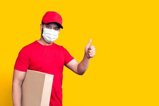 Dipendente dell'uomo di consegna in maschera facciale uniforme della maglietta in bianco del cappuccio rosso tiene la scatola di cartone vuota isolata su fondo giallo