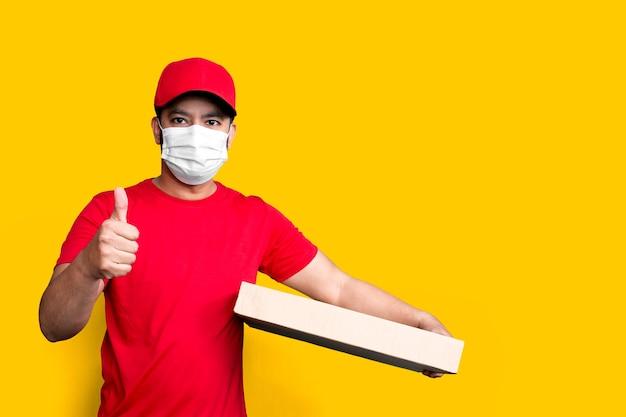 Dipendente dell'uomo di consegna nella maschera facciale uniforme della maglietta in bianco del cappuccio rosso tiene la scatola di cartone vuota isolata su giallo
