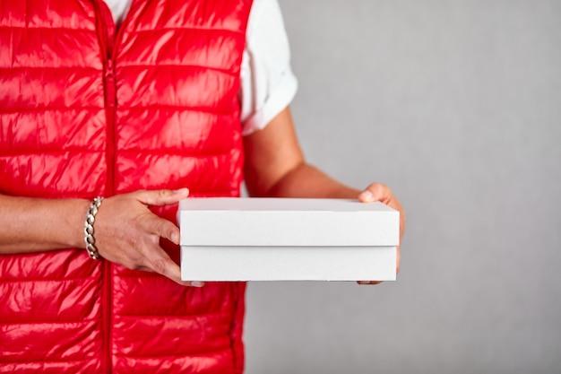 Il dipendente del fattorino in uniforme rossa della maglia tiene la scatola di cartone vuota isolata