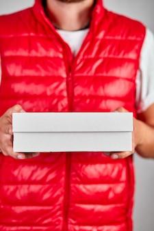 Il dipendente del fattorino in uniforme rossa della maglia tiene la scatola di cartone vuota