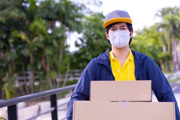 Impiegato del fattorino che indossa una maschera e che tiene le scatole fuori.