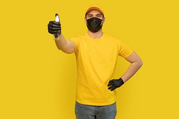 Dipendente del fattorino in uniforme gialla della maglietta, maschera sterile, sapone disinfettante per bottiglia della stretta del guanto isolato