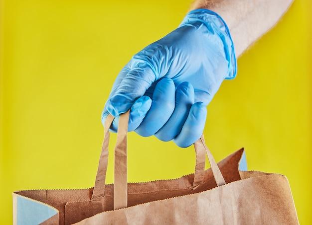 Il datore di lavoro del fattorino in guanti blu tiene il sacco di carta del mestiere con alimento, isolato sullo studio giallo. servizio quarantena pandemia coronavirus virus concept 2019-ncov.