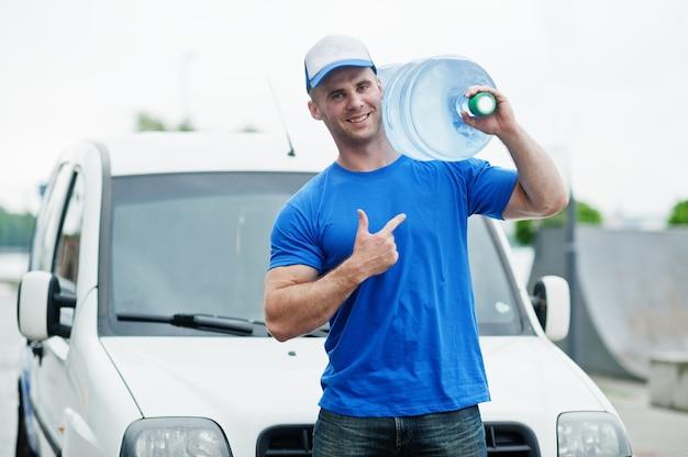 Uomo di consegna davanti al furgone che consegna bottiglie d'acqua
