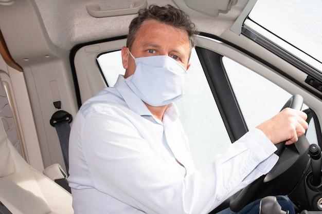 Uomo di consegna in maschera medica fatta a mano in auto durante il coronavirus, quarantena di infezione da malattia di covid-19