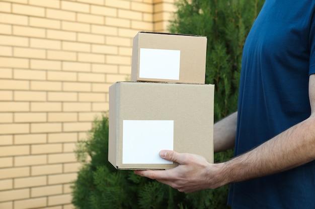 Il fattorino tiene le scatole in bianco all'aperto, spazio per testo