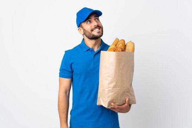 Uomo di consegna che tiene una borsa piena di pane isolato su bianco che osserva in su mentre sorride