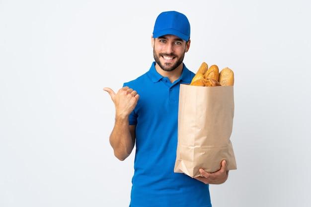 Fattorino che tiene una borsa piena di pane che punta di lato per presentare un prodotto