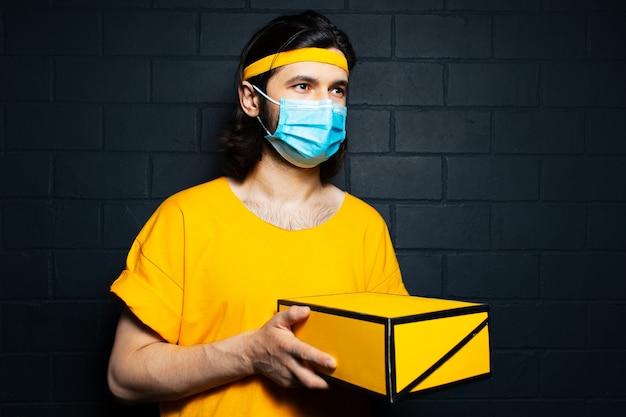 Fattorino che tiene una scatola che indossa maschera medica e camicia gialla sullo sfondo del muro di mattoni neri.