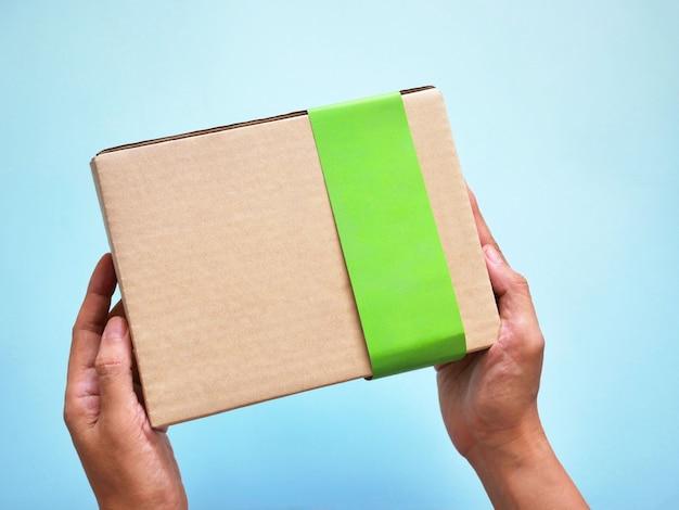 Uomo di consegna che tiene la scatola di cartone.