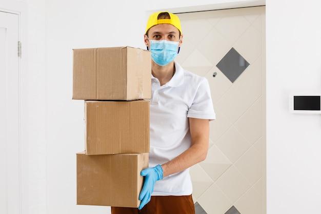 Fattorino che tiene scatole di cartone in guanti di gomma medica e maschera. copia spazio. trasporto di consegna veloce e gratuito. acquisti online e consegna espressa. quarantena