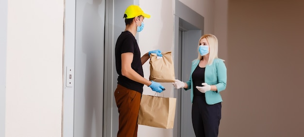 Fattorino che tiene scatole di cartone in guanti di gomma medica. quarantena. coronavirus. consegna a domicilio