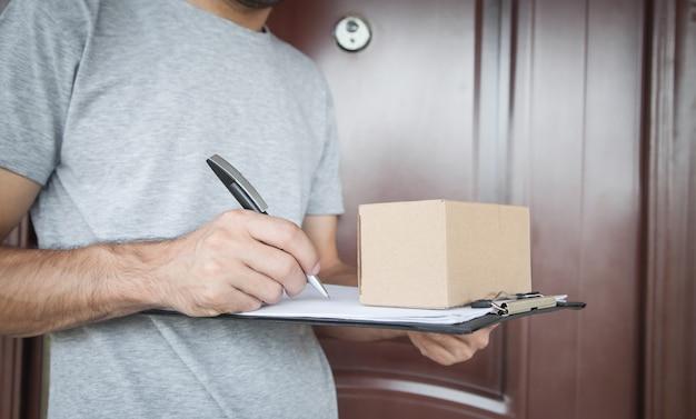 Uomo di consegna che tiene cassetta dei pacchi e appunti