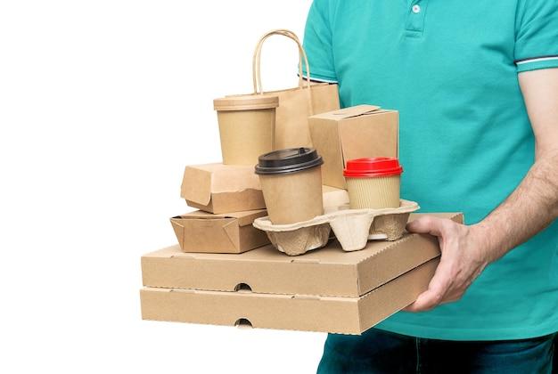 Fattorino che tiene vari contenitori per alimenti da asporto, scatola per pizza, tazze da caffè nel supporto e sacchetto di carta isolato su bianco.