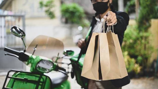 Un fattorino tiene in mano un pacco mentre è in piedi accanto alla sua motocicletta.