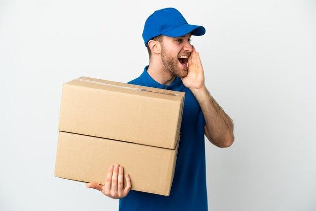 Uomo di consegna su sfondo bianco isolato che grida con la bocca spalancata di lato