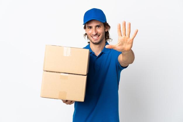 Uomo di consegna isolato sul muro bianco che conta cinque con le dita