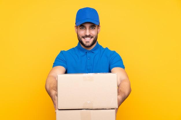 Uomo di consegna sopra giallo isolato con espressione felice
