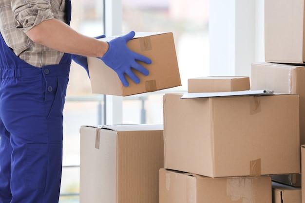 Uomo di consegna scatole per trasloco al chiuso