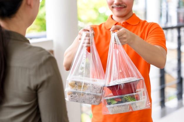 Uomo di consegna in uniforme arancione consegna cibo asiatico in scatole da asporto a un cliente donna a casa