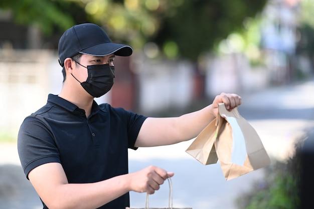 Uomo di consegna in maschera protettiva che consegna cibo al cliente sulla porta