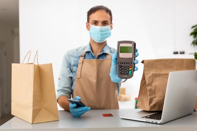 Il fattorino con maschera protettiva e guanti tiene in mano il terminale pos. servizio quarantena pandemia coronavirus virus concetto