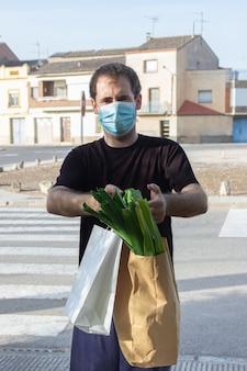 Uomo di consegna in maschera protettiva e guanti medicali in possesso di un sacchetto di carta. servizio di consegna in condizioni di pandemia di coronavirus covid-19