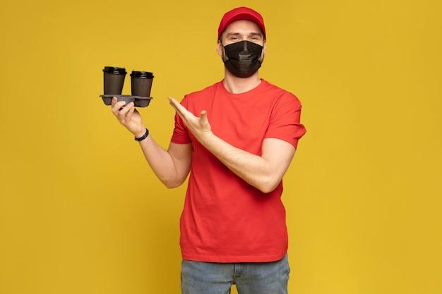 Uomo di consegna in guanti di maschera uniforme t-shirt bianca berretto rosso isolati sulla parete gialla