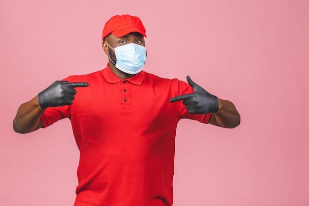 Uomo di consegna in guanti di maschera facciale sterili uniformi della maglietta in bianco del cappuccio rosso. dito puntato.