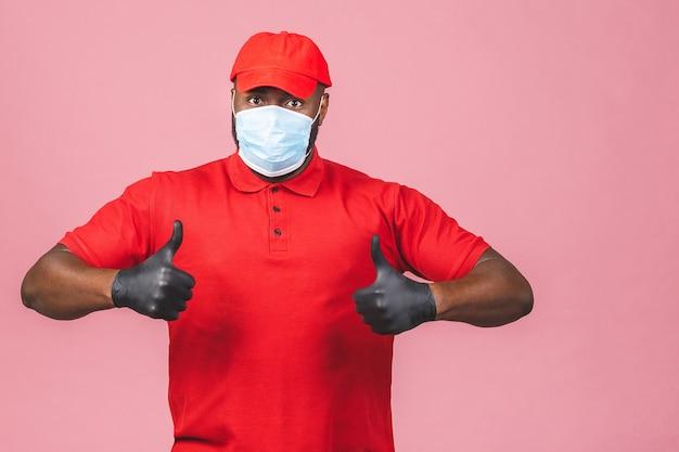 Uomo di consegna in guanti di maschera facciale sterili uniformi della maglietta in bianco del cappuccio rosso. pollice su.